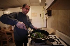 Tek Nepal prepara curry seco para el almuerzo de ese día.