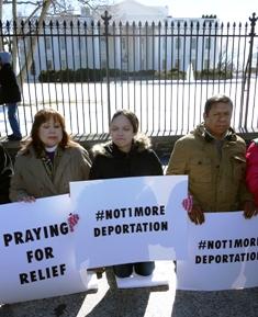 La obispa de la Iglesia Metodista Unida de Los Ángeles, Minerva Carcaño y la hija de un inmigrante detenido, Pilar Molina, con Pablo Alvarado rezan arrodillados frente a la Casa Blanca.