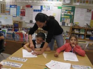 La Maestra González ayuda a una niña en la Academia Bridges. Foto: Zaidee Stavely