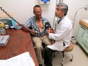El doctor William Martínez, de la clínica Samarita de Los Ángeles que revisa un paciente, dice que son muchos los riesgos que viven quienes están en espera de recibir su tarjeta de seguro de Medi-Cal.