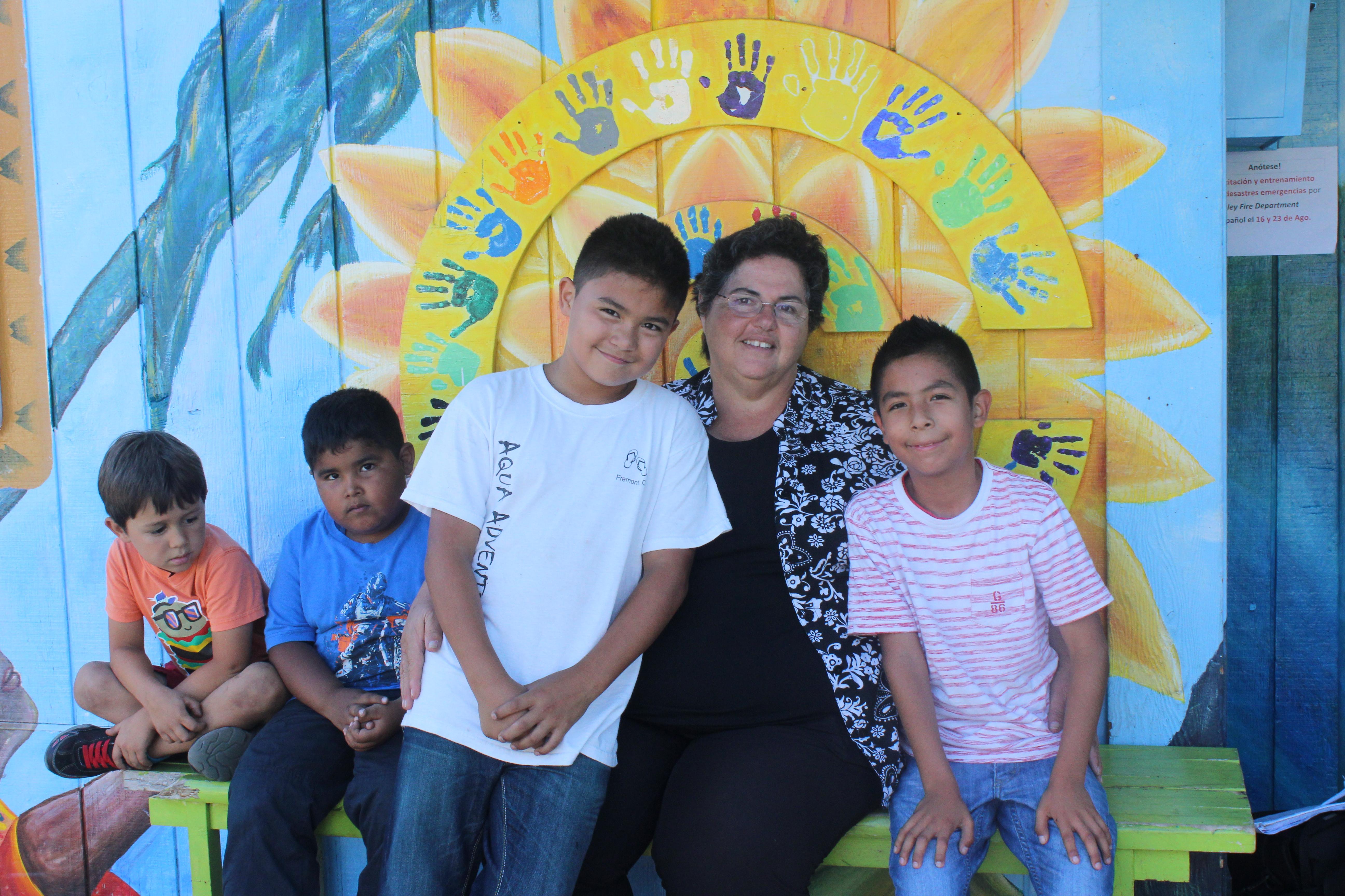 Martha Cueva con unos niños del programa extraescolar del Instituto del Área de la Bahía para el Progreso Hispano. Foto: Clara Roig Medina.