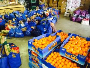 Antes de repartir las bolsas de comida los voluntarios se encargan de acomodar las frutas y verduras.