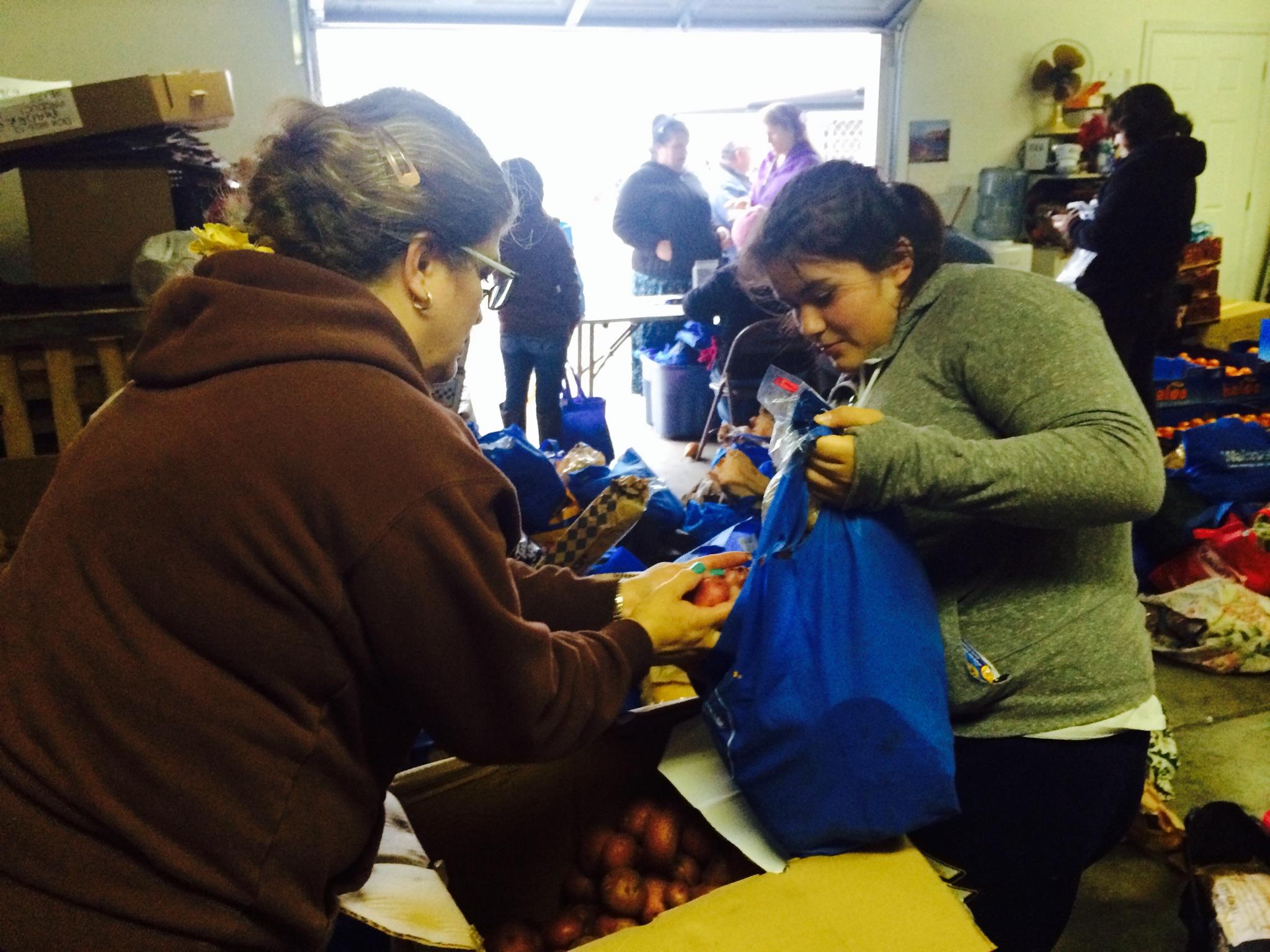 Un voluntario ayuda la a una señora con sus bolsas de comida.