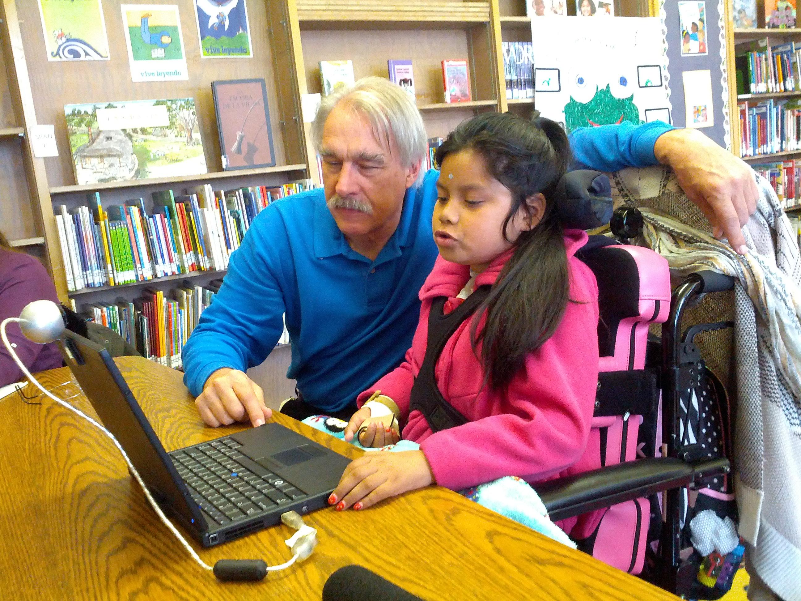 Un especialista en tecnología del distrito de Oakland, Chris Beatty, le ayuda a Jacqueline a usar una computadora para leer. Foto: Zaidee Stavely.