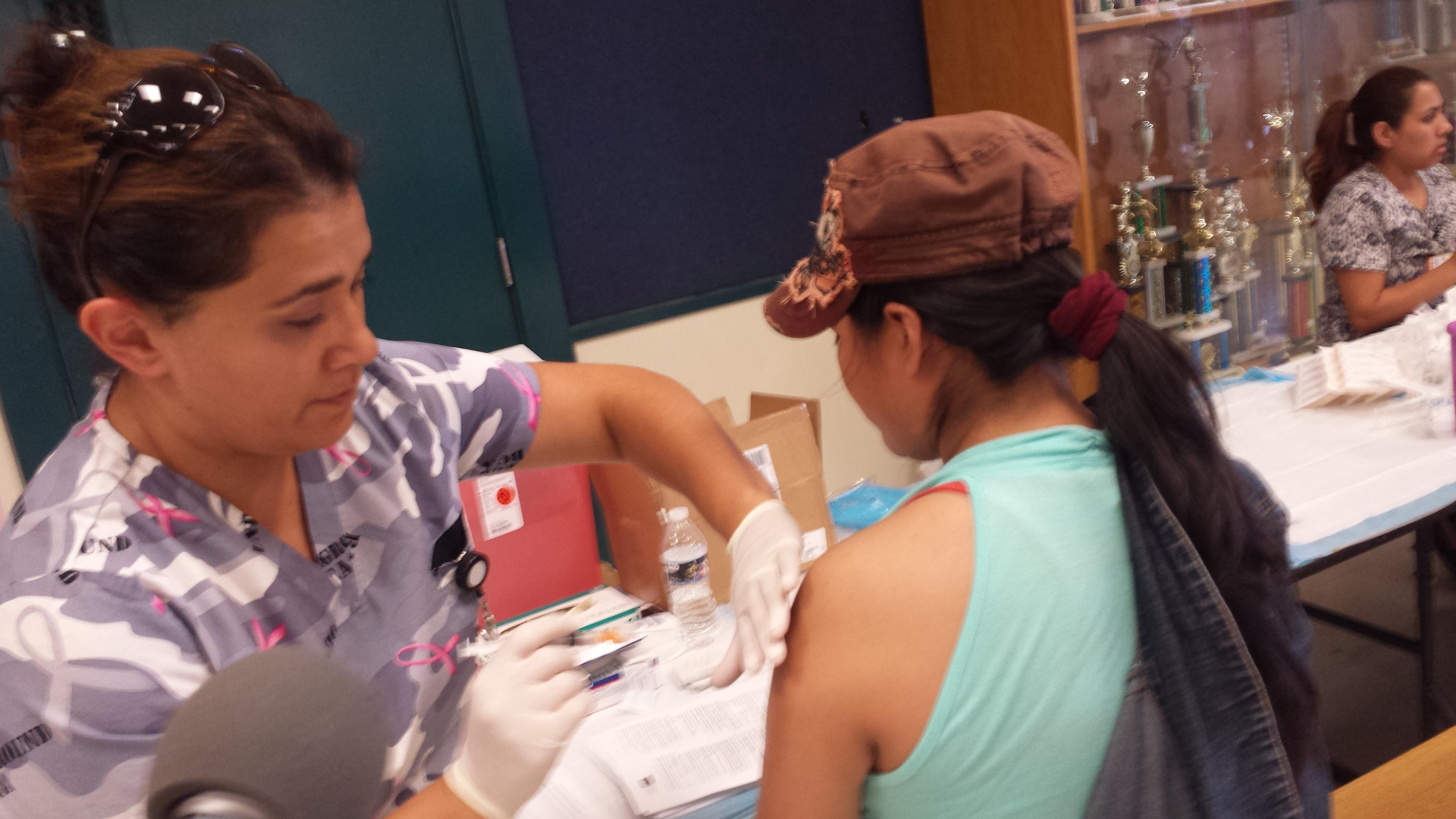 Madre de familia recibe vacuna contra la gripe