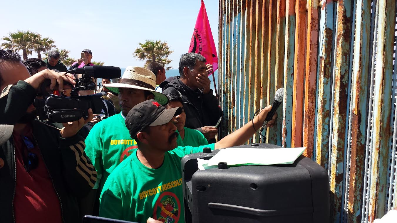 Ayudado con un micrófono para escuchar el mensaje de los jornaleros del lado de San Ysidro, un trabajador agrícola mexicano recoge la voz que viene del otro lado. Foto: Rubén Tapia.
