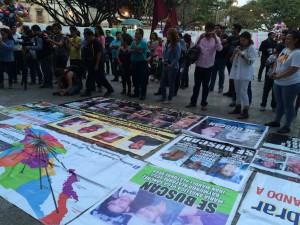 Miembros de la caravana despliegan carteles con las fotos de sus seres queridos desaparecidos. Foto: Raúl Silva.