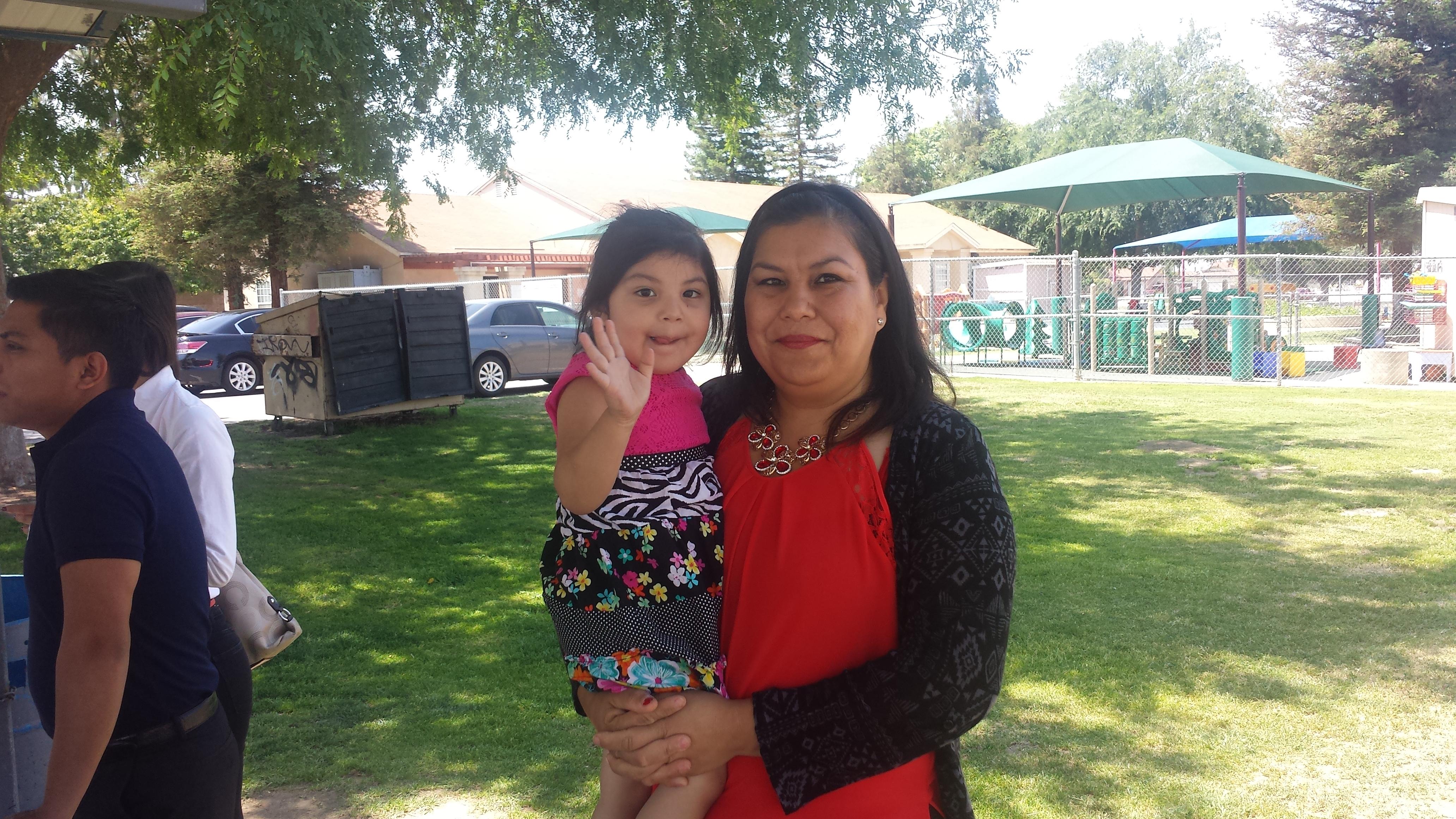 Claudia Angulo se prepara para una conferencia de prensa, carga a una de sus cuatro hijos.