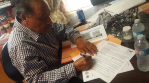Everardo Suárez  firma consentimiento para conectarse a la red de agua de Porterville. Foto: Rubén Tapia.