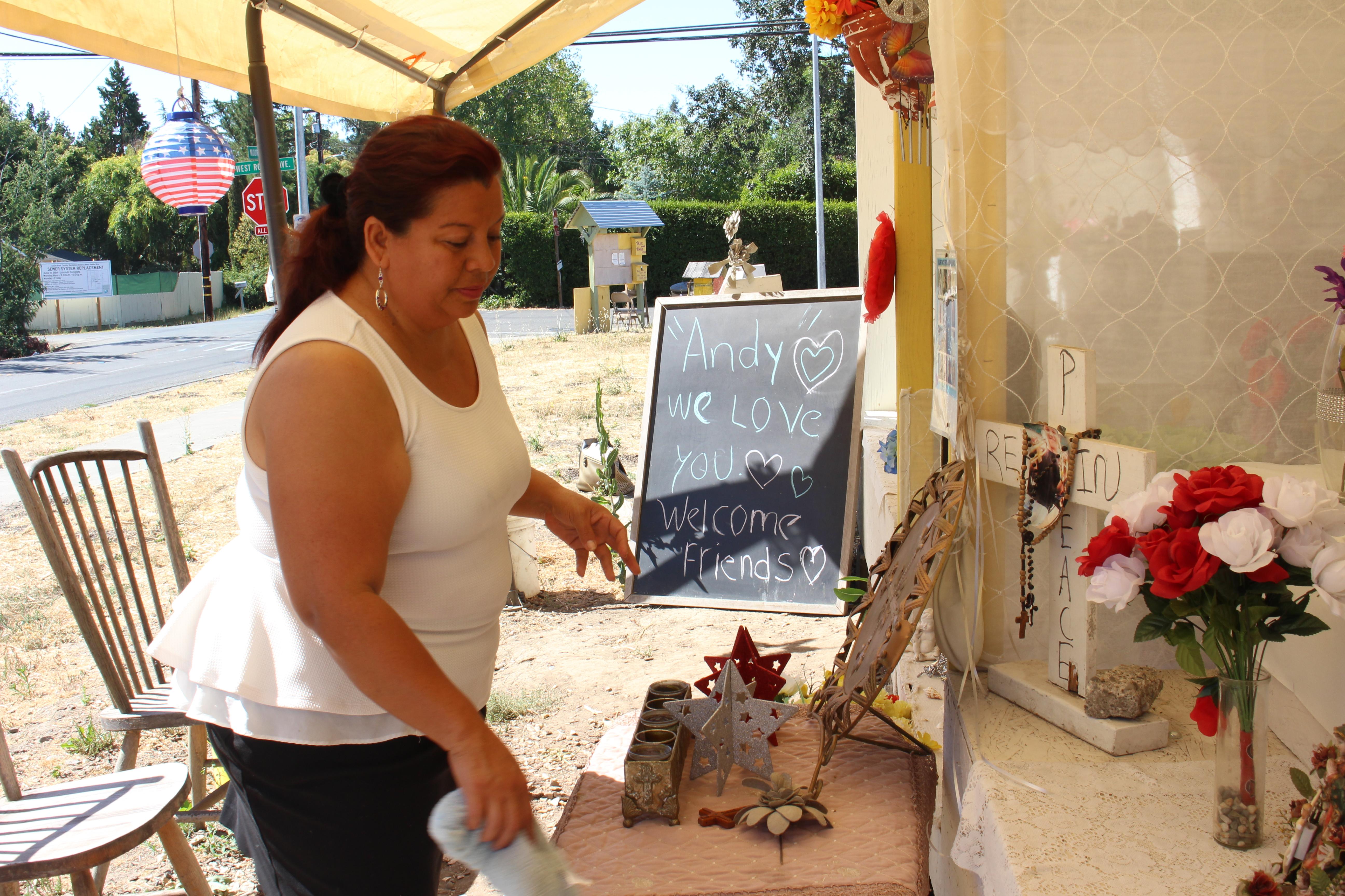 """Concepción Domínguez limpia un altar para Andy López en el lugar donde murió. Vecina de López, dice que preferiría que Gelhaus no patrullara las calles. """"Es demasiado peligroso"""". Foto: Farida Jhabvala Romero/KQED"""