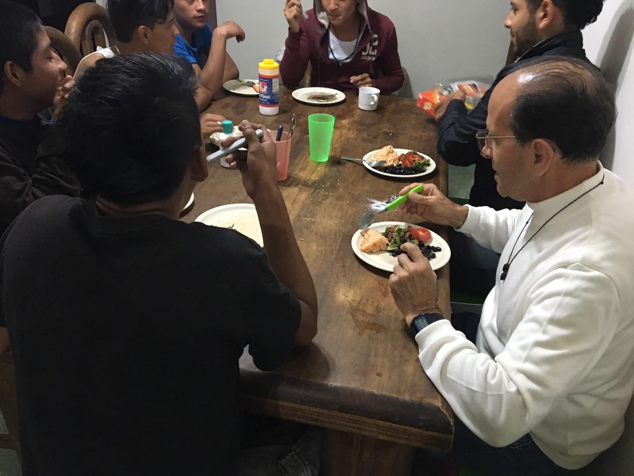 El padre Alejandro Solalinde cenando con los jóvenes en el albergue.