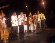 Jacobo Hernández anuncia reconocimiento a Violeta Quintero, que está a un lado de su harpa. Foto: Rubén Tapia.
