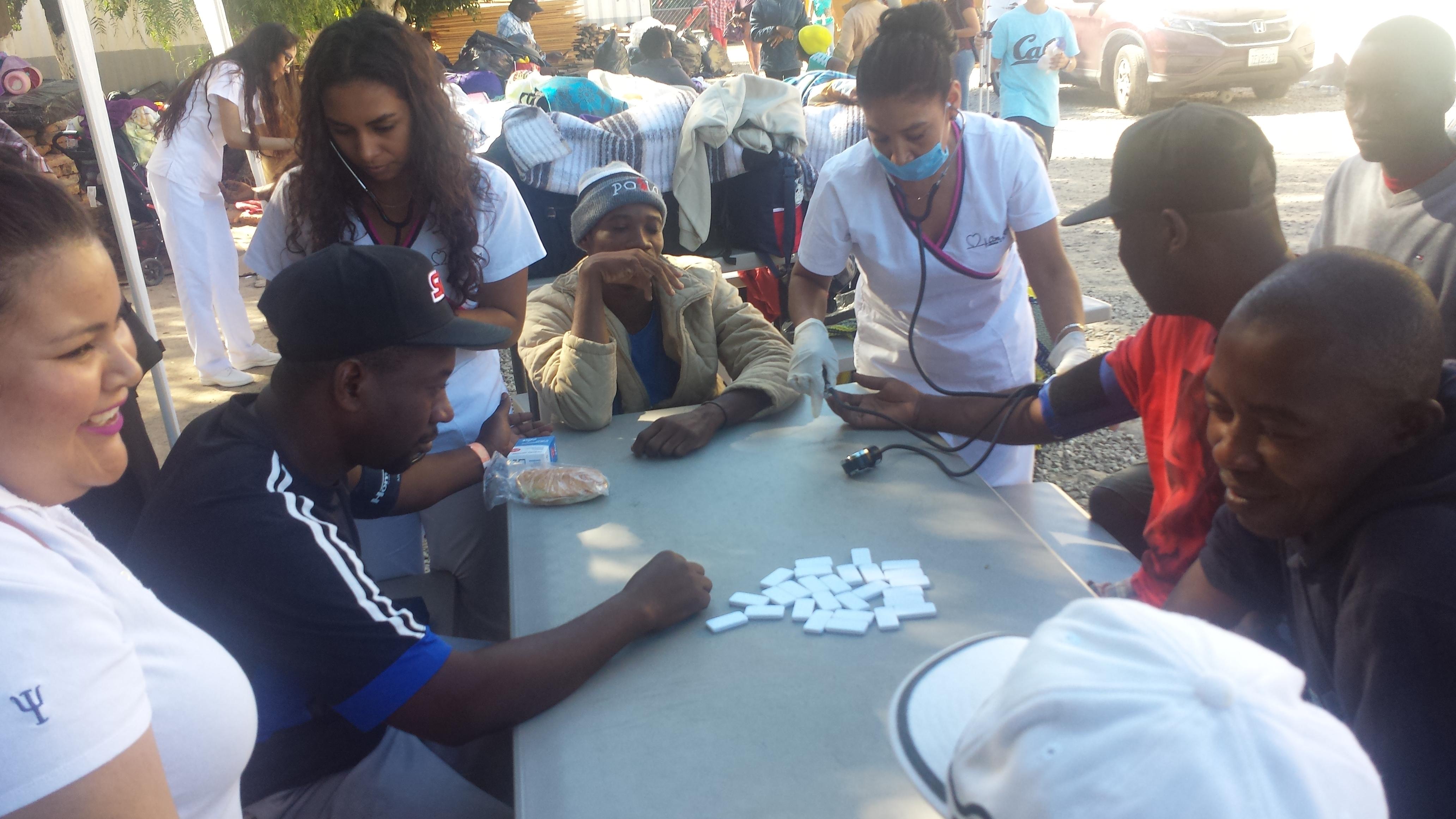 Estudiantes de enfermería de la escuela, Con Amor,  toman la presión de migrantes haitianos que juegan domino.