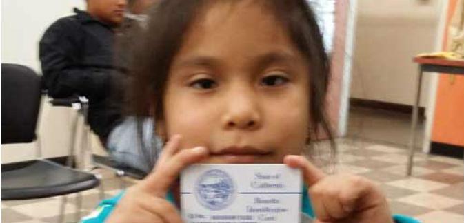 Esta niña inmigrante muestra con orgullo su credencial de Medi-Cal, que le da acceso a una cobertura completa que incluye dentista, con la nueva ley de California, SB 75.