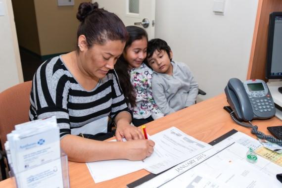 Guadalupe Carrera, de 36 años, con su hija Eva Maqueda, de 9, y su hijo José Maqueda, de 5, llenan una solicitud de asistencia con el seguro médico en la Clínica de Atención Médica Familiar El Proyecto Del Barrio. Foto: Heidi de Marco / California Healthline.