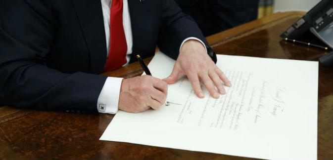 Trump firmando órdenes ejecutivas.