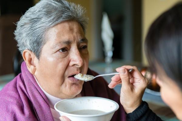 Tania Yanes alimenta con avena a su mamá, Blanca Rosa Rivera, el domingo 27 de noviembre de  2016. Foto: Heidi de Marco/KHN.