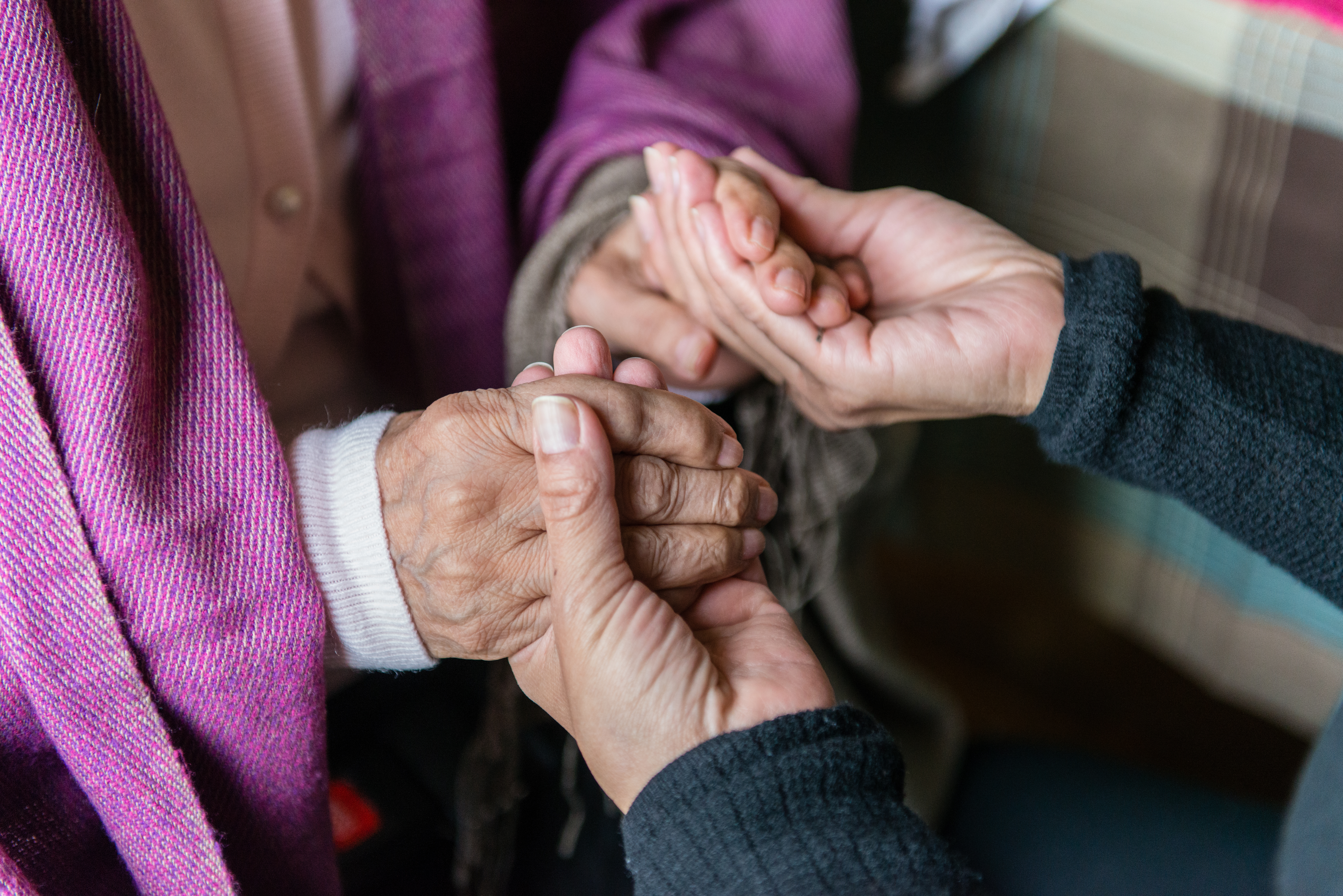"""Tania Yanes holds her mother's hands on Sunday, November 27, 2016. """"I try to make her feel comfortable, feel safe."""" said Yanes. (Heidi de Marco/KHN)"""