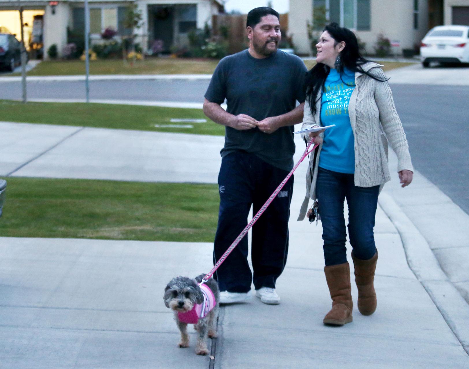 Juan y Julie Solís llevan habitualmente a su perra Gigi a dar un pequeño paseo por el vecindario después del atardecer. Foto: Casey Christie / The Bakersfield Californian.