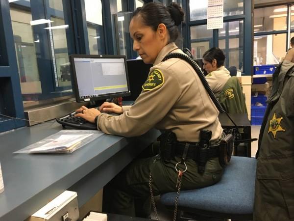 Alguacil Elisa Magallanes tomando información de un detenido