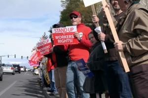Manifestantes desplazados de sus empleos se alinean en las calles cerca de la jefatura de T-Mobile durante una manifestación que desacreditaba la decisión de la compañía de cerrar siete centros de llamadas. Foto: Bellevue Reporter.