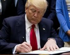 Donald Trump firmando una orden ejecutiva.