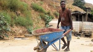Antony Francis es el que más entiende español. Prepara el cemento para los pisos de la casa de la Pequeña Haití.