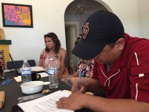Los participantes de una clínica legal firman un contrato en el que se comprometen a ser voluntarios con Trans Queer Pueblo e invitar a otros a futuros entrenamientos.