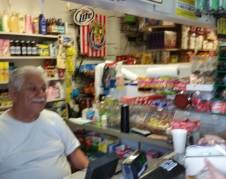 Miguel Quintero despacha a una clienta en su negocio_'Yoli's Market'.