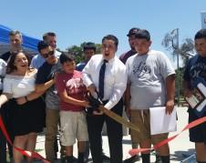 Alcalde Gurrola y joven patinador cortan listón que inaugura oficialmente la pista de patinaje de Arvin, en el parque Di Giorgio.