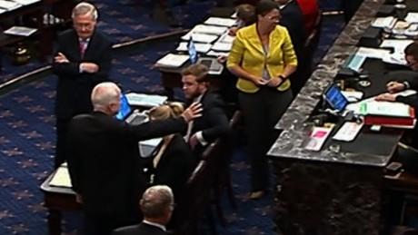 El senador republicano de Arizona, John McCain –de espaldas con el brazo extendido, que tornará en un pulgar hacia abajo- en el Senado, en el momento de decir ¡NO! al proyecto de ley de salud de los republicanos. En el fondo, Mitch McConnell compungido. Foto: CNN.