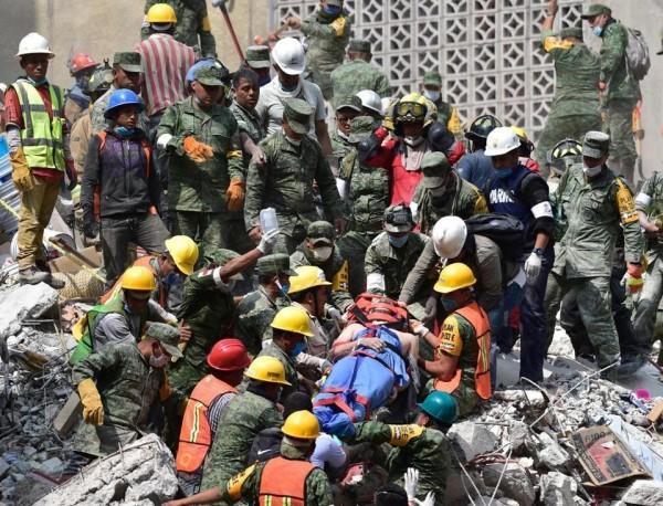 Socorristas rescatan a una víctima alzándola desde el interior de una estructura derrumbada. Foto: The Globo de Boston.