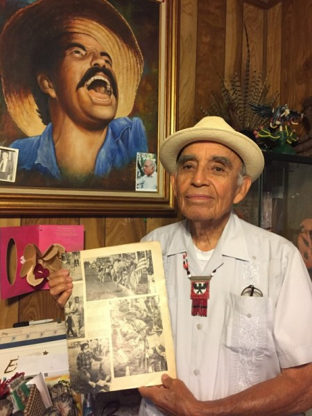 Alfredo Acosta Figueroa holds an edition of Times Magazine where his picture was published singing in support of the peasants with César Chávez and also inspired the portrait that appears behind him in this photo.
