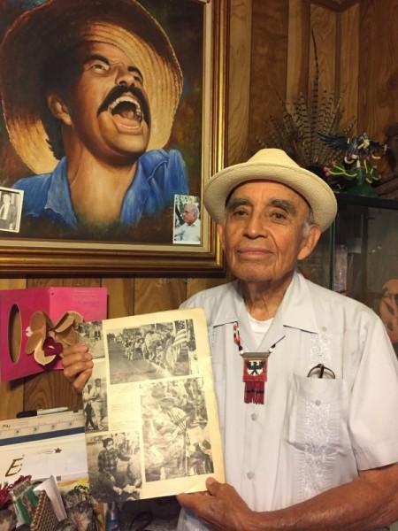 AAlfredo Acosta Figueroa sostiene una edición de Times Magazine donde se publicó su foto cantando en apoyo a los campesinos con César Chávez y que además inspiró el retrato que aparece detrás suyo en esta foto.