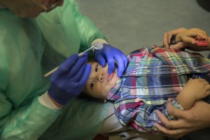 Ray Stewart, a pediatric dental professor at the University of California-San Francisco, examines Matthew Mai, 2, of Vallejo, Calif. Stewart has been treating infants for more than 15 years. (Robert Durell for Kaiser Health News)