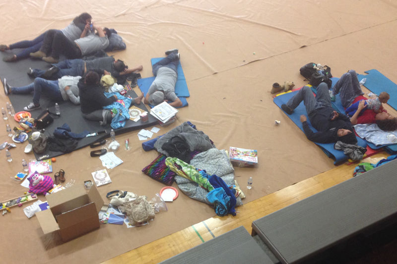Evacuees stretch out in the Analy High School gym in Sebastopol.      Photo by Bleys Rose