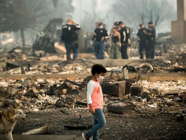 Un niño pasa mientras los agentes de policía buscan indicios que los conduzcan a encontrar algunas de las posibles causas de los incendios en Coffey Park. Foto: ABC News.