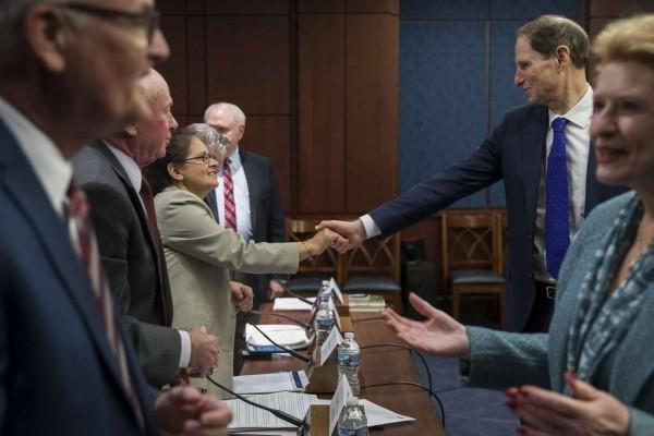 El senador Ron Wyden (D-OR) le estrecha la mano a Luz Arévalo, abogada de una clínica de preparación de impuestos de bajos ingresos en Boston, al comienzo de una reunión sobre el plan de impuestos del Partido Republicano realizada por Políticas Democrática y Comunicaciones. Foto: Drew Angerer, Getty Images.