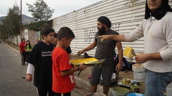 Luís Marmolejo con gorra negra instruye a niños en Tecate.