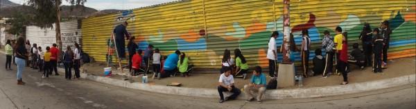 Menores de escuelas locales se suman a pintar a Quezalcóatl sobre el muro fronterizo.