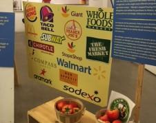 Un ángulo del interior de la carpa, que capta un letrero con los logos de mega empresas que firmaron con la coalición de Trabajadores Agrícolas poco más de media década atrás el Acuerdo de Comida Justa. Foto: MVG.