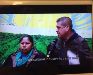 Gerardo Reyes y Guadalupe Gonzalo, de la Coalición de Trabajadores de Immokalee hablando sobre la industria de la comida y los campos de cultivo, en un video reproducido a través de una tableta electrónica colgada en la pared interior de la carpa museo, en la exhibición de la campaña 'Cosecha sin Violencia', en el Lower East Side Girls Club en el bajo Manhattan.