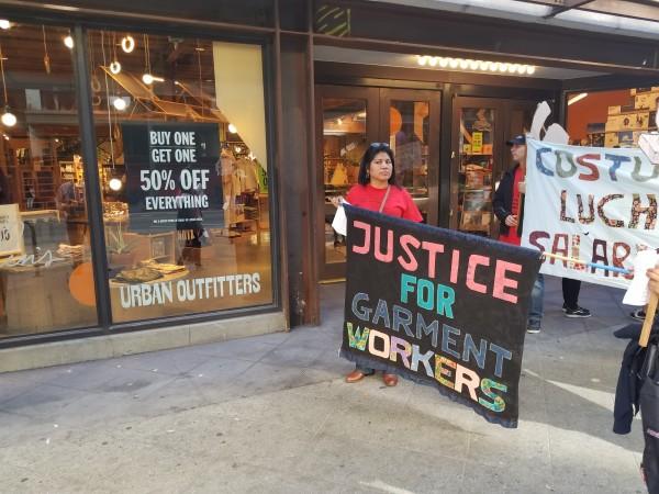 Maribelia Quiroz sostiene una manta frente a la  tienda Urban Outffiters que cerró sus puertas por la protesta.