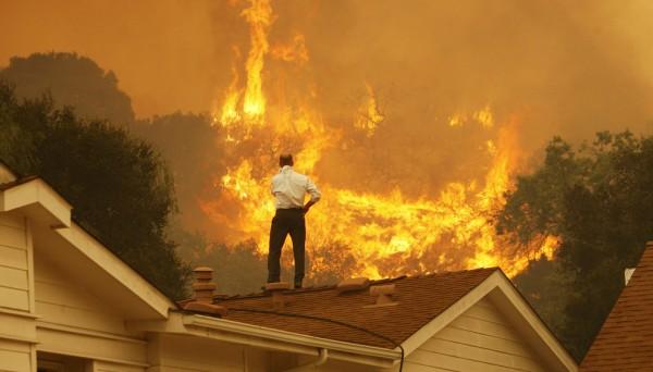 Propietario de una costosa casa mira desde el techo como las llamas se ven venir. Foto: www.boston.com