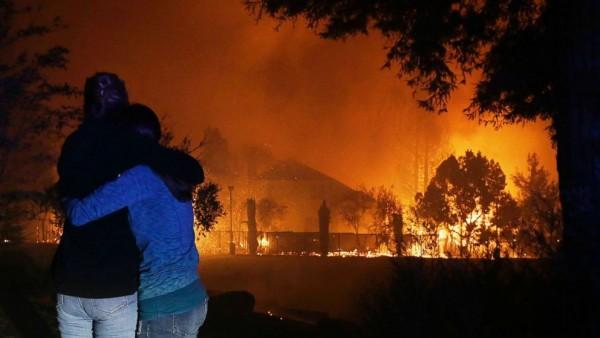 Atónitos y abrazados una pareja ver la destrucción del fuego en Ventura, California. Foto: Abc7.com