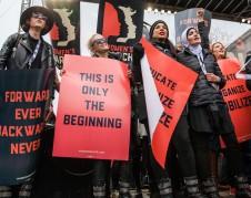 """Cinco mujeres se paran con carteles de protesta mirando hacia el aire, con un letrero que dice: """"Esto es apenas el comienzo"""", en la Marcha de Mujeres en Washington, DC, el 21 de enero de 2017. Foto: www.powertothepolls.com."""