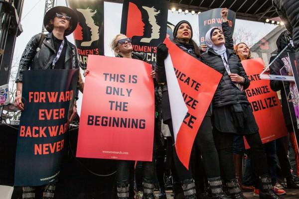 Cinco mujeres se paran con carteles de protesta mirando hacia el aire, con un letrero que dice:
