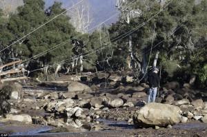 Un hombre se para debajo de cables de electricidad derribados y en medio de rocas rodadas arroyo abajo, que ahora se colocan en el lugar de las carreteras en Montecito Foto Ap.