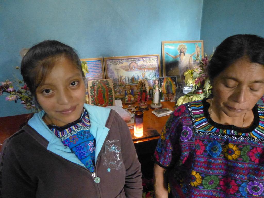 Martina y su madre Aureliana frente al altar de su casa.