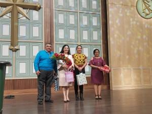 Gustavo Santiago, con el ramo de flores la licenciada Aida Ruiz García, Directora del Instituto Oaxaqueño de Atención al Migrante.